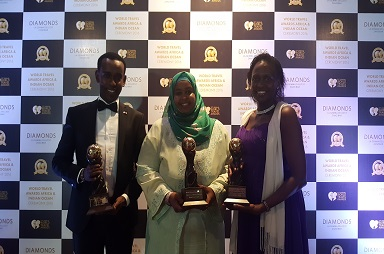 Mrs Fatuma Hirsi Mohammed , PS Tourism' is joined by Daudinn Haji , Ministry of Tourism , left  and Wausi Walya of KTB  (left)  to receive some of the awards Kenya was recognized for at the 23rd edition of the world Travel Awards.
